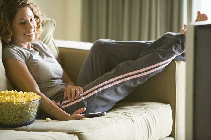 Woman relaxing with feet up on couch watching TV